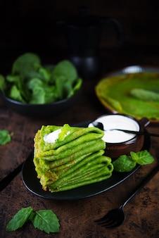 Spinazie dunne pannenkoeken zijn groen op een houten tafel. verticale foto.