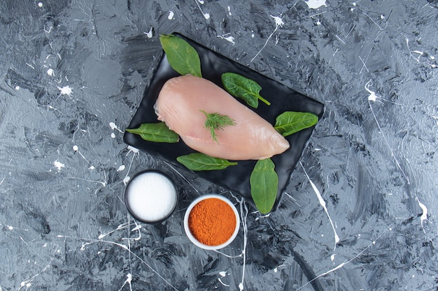 Spinazie en kipfilet op een schaal naast kruiden- en zoutkommen, op het marmeren oppervlak.