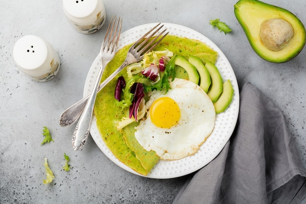 Spinazie groene pannenkoeken (pannenkoeken) met gebakken ei, avocado en bladeren van mix van salade op keramische plaat op grijs betonnen oppervlak. bovenaanzicht. koperen ruimte.