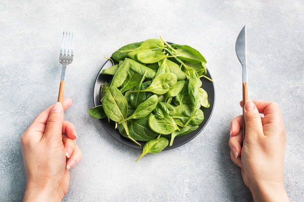Spinazie groene verse bladeren op een zwarte plaat. mes en vork in de handen van een vrouw, een maaltijd.