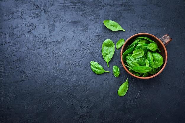 Spinazie in de kom op de donkere achtergrond. gewassen verse mini-spinazie, vitaminesalade.