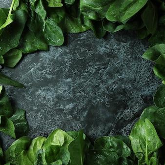 Spinazie op zwart smokey-oppervlak, ruimte voor tekst