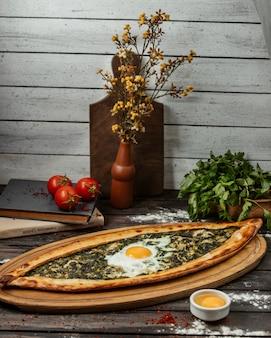 Spinazie pide met ei op houten portie bord