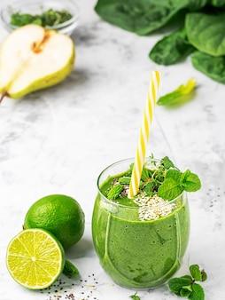 Spinazie smoothie met fruit en zaden superfoods, versierd met muntblaadjes in een glazen beker