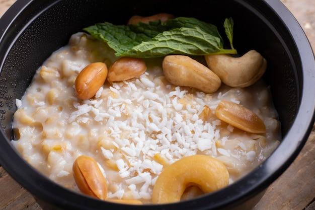 Spinazie, witte bonen gerst pap. detailopname. noten en muntblad voor het ontbijt