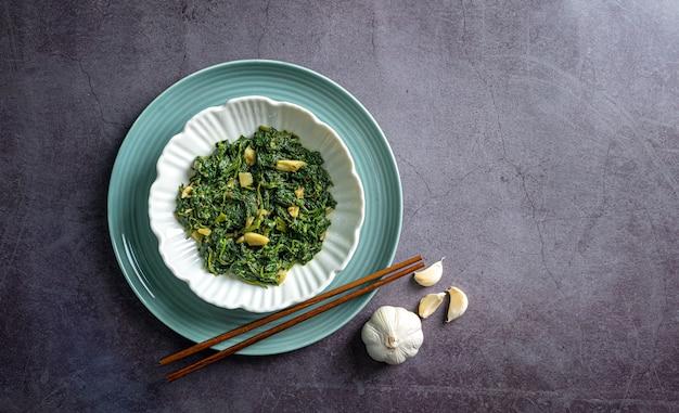Spinaziecurry in witte kom en blauw bord met eetstokje en teentje knoflook op zwarte leisteen tegel bovenaanzicht