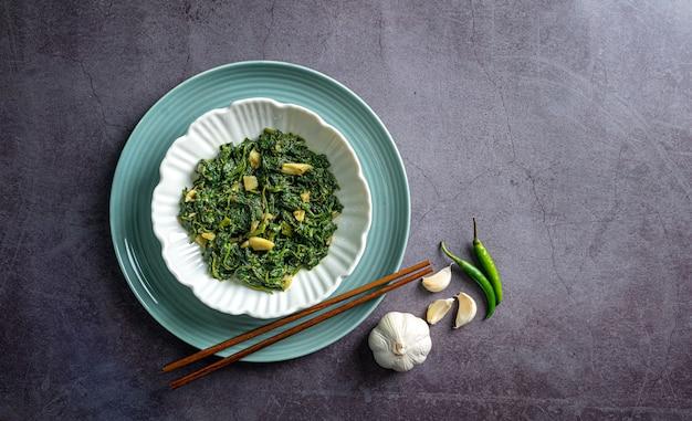 Spinaziecurry in witte kom en blauw bord met eetstokje knoflookteentje pepers op zwarte leisteen tegel bovenaanzicht