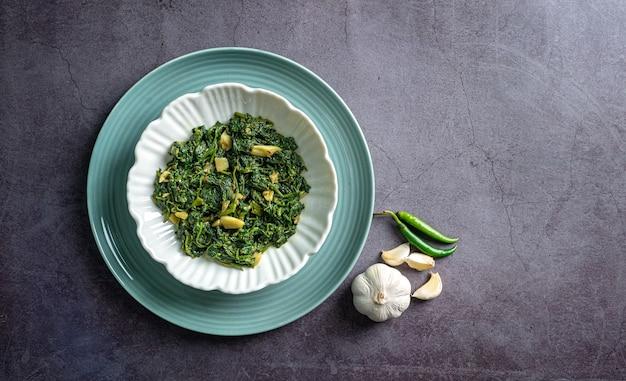 Spinaziecurry in witte kom en blauw bord met knoflook en kruidnagelpepers op zwarte leisteen bovenaanzicht