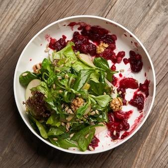 Spinaziesalade in een witte kom. gezonde dieetsalade met spinaziebladeren, okkernoten, fruit en groente