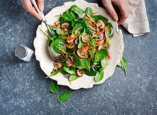 Spinaziesalade met gesherriede paddestoelen en wortelen. vrouwelijke hand die salade mengt