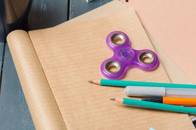 Spinner, notitieboekje en potlood op de tafel