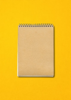 Spiraal gesloten notitieboekje, bruine papieren omslag, geïsoleerd op gele achtergrond