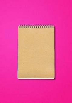 Spiraal gesloten notitieboekje, bruine papieren omslag, geïsoleerd op roze achtergrond