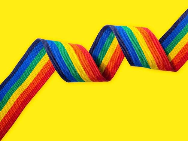 Spiraal regenboog strip lint horizontale stijl geïsoleerd op heldere gele achtergrond met kopie ruimte. lgbt-concept met trotskleuren en regenboogvlagstrook.