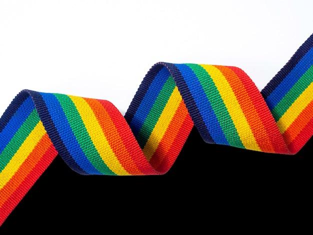 Spiraal regenboog strip lint horizontale stijl geïsoleerd op zwarte en witte achtergrond met kopie ruimte. lgbt-concept met trotskleuren en regenboogvlagstrook.