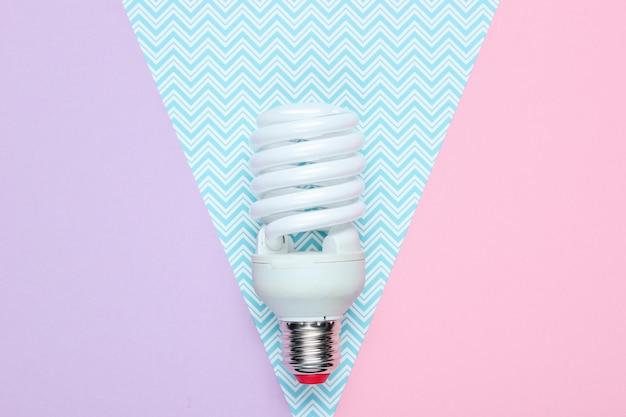 Spiraal spaarlamp op pastel papier tafel. bovenaanzicht