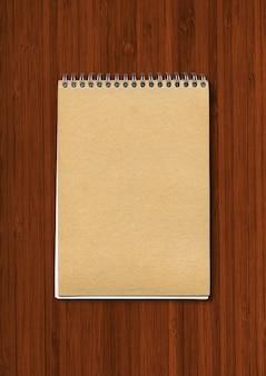 Spiraalvormig gesloten notitieboekje, bruine papieren omslag, geïsoleerd op een donkere houten ondergrond