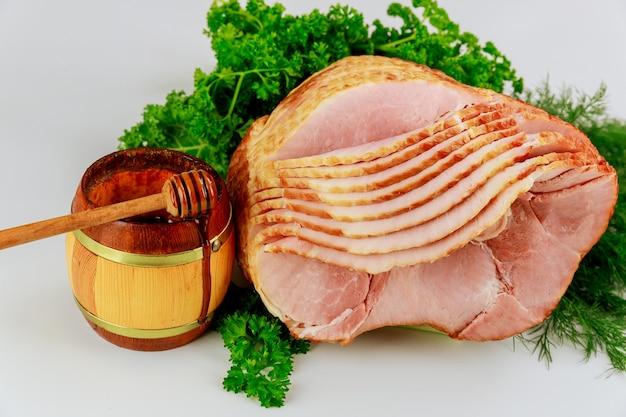 Spiraalvormig gesneden hickory gerookte ham met verse kruiden en honing. vakantie eten.