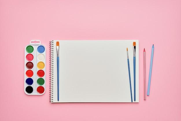 Spiraalvormig notitieblok met potloden, penselen en aquarelverf