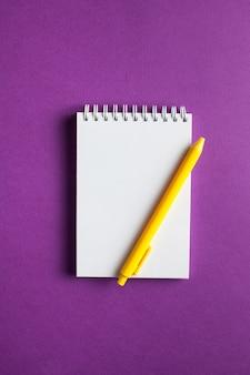 Spiraalvormig notitieboekje met pen als mockup voor ontwerp op een gekleurd oppervlak