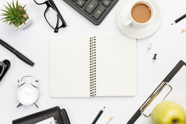 Spiraalvormige blocnote die met stationeries, appel en koffie op wit bureau wordt omringd
