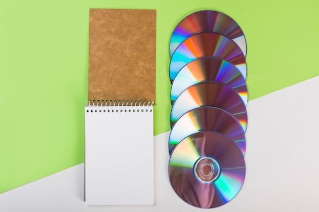 Spiraalvormige blocnote met kleurrijke compact-discs op groene en witte dubbele achtergrond