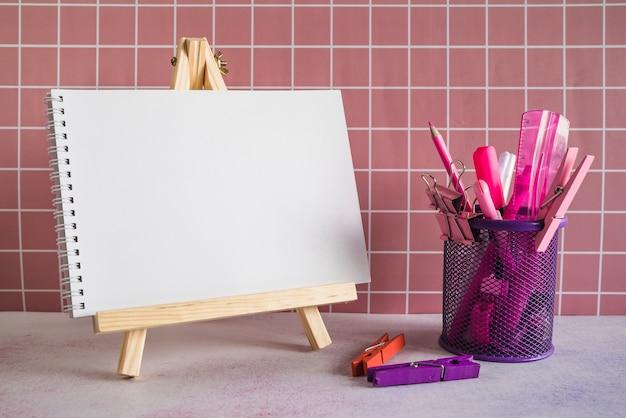 Spiraalvormige blocnote op houder en roze kantoorbehoeften