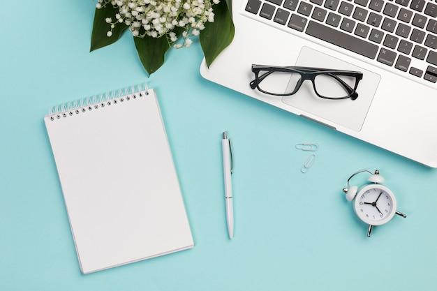 Spiraalvormige blocnote, pen, paperclip, wekker, oogglazen op laptop met lelietje-van-dalenboeket op blauw bedrijfsbureau