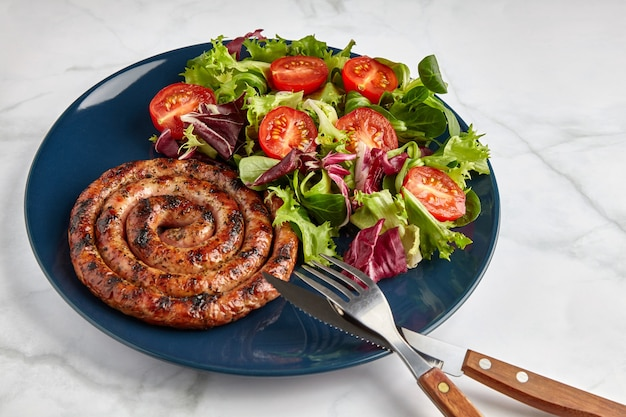 Spiraalvormige gegrilde worst met tomaten en kruiden op een blauw bord met bestek op een marmeren tafel