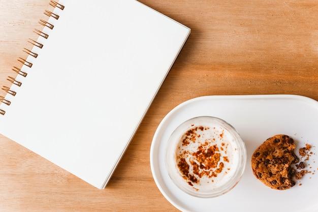 Spiraalvormige lege blocnote en koffieglas met gegeten koekjes op houten lijst