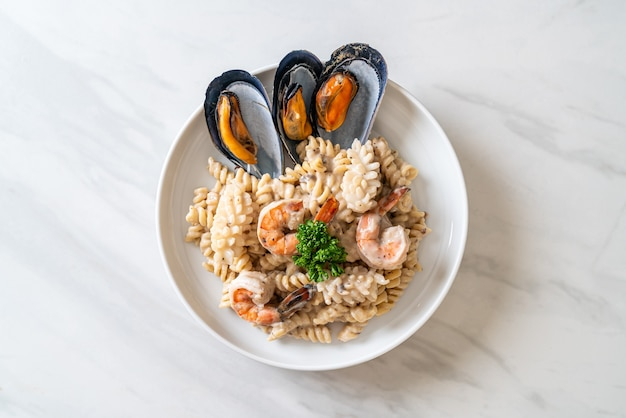 Spiraalvormige pasta champignonroomsaus met zeevruchten - italiaanse keukenstijl