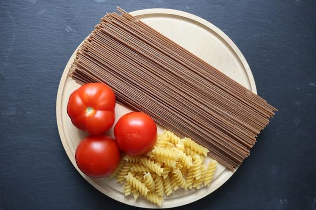 Spiraalvormige pasta en tomaten, donkerbruine spaghetti op een rond bord op een zwart oppervlak