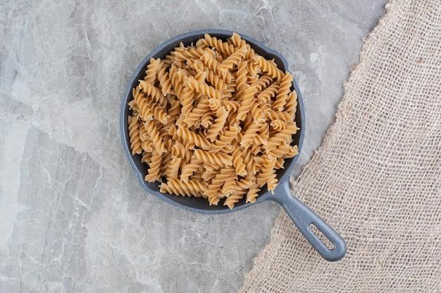 Spiraalvormige pasta's in een ijzeren pan op het marmer
