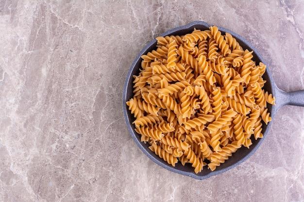 Spiraalvormige pasta's in een zwarte ijzeren pan