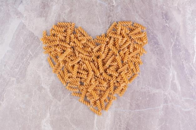 Spiraalvormige pasta's in hartvorm op het marmer.