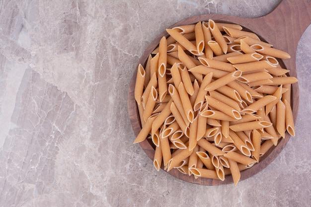 Spiraalvormige spaghetties in een rustieke houten beker op het marmer