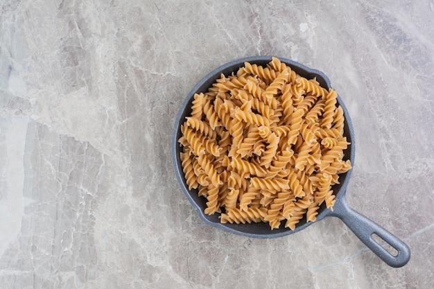Spiraalvormige zelfgemaakte pasta's in een zwarte pan.