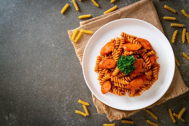 Spiral of spirali pasta met tomatensaus en worst - italiaanse keukenstijl