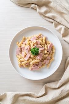 Spirali of spiraalvormige pasta champignonroomsaus met ham - italiaanse keukenstijl