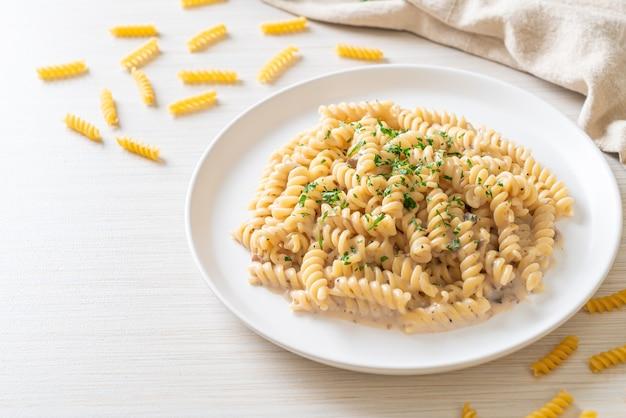 Spirali of spiraalvormige pasta champignonroomsaus met peterselie - italiaanse keukenstijl