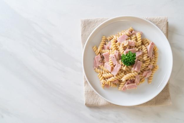 Spirali of spiral pasta champignonroomsaus met ham. italiaanse eetstijl