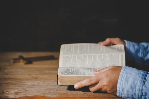 Spiritualiteit en religie, handen gevouwen in gebed op een heilige bijbel in kerkconcept voor geloof.