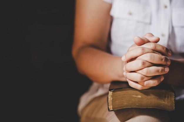 Spiritualiteit en religie, handen gevouwen in gebed over een heilige bijbel in kerk-concept voor geloof.