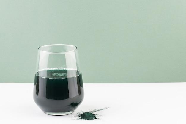 Spirulina-drankje in een glas op een witte tafel, groene ruimte, minimalisme