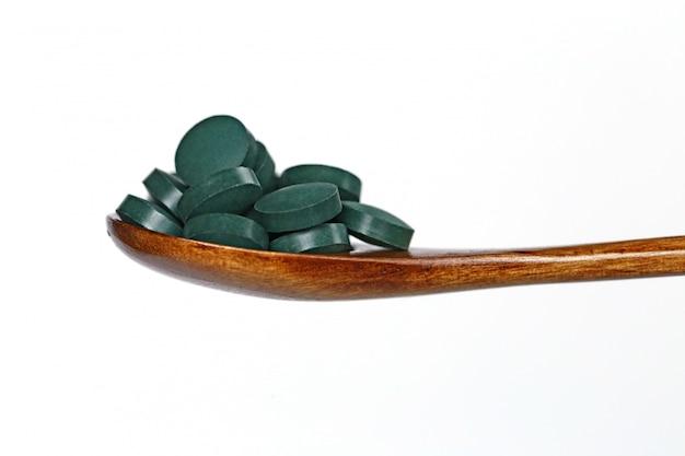 Spirulina in tabletten in een houten lepel op een geïsoleerd wit