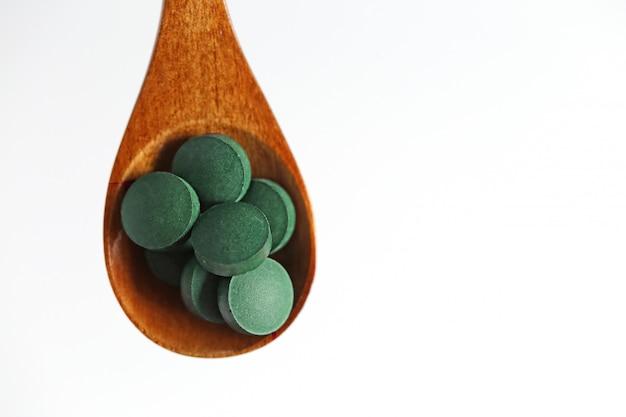 Spirulina in tabletten in een houten lepel