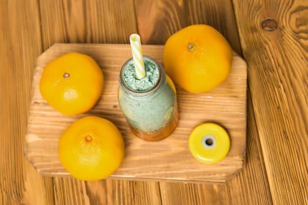 Spirulina smoothie op een houten bord naast sinaasappelen