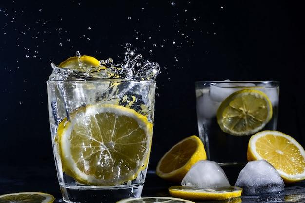 Splash gin-tonic cocktail met schijfjes citroen ijsblokje valt in water met citroen kopieer ruimte, limonade