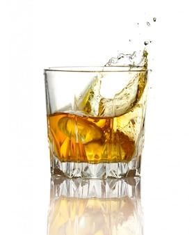 Splash in glas whisky en ijs geïsoleerd