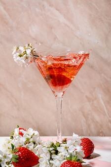 Splash van aardbei alcoholische of niet-alcoholische cocktail in glas versierd met bloeiende takken van kersenboom over witte en roze muur